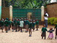 This is some of our kindergarten children near the front gate with the Principal of Wisdom Academy- Richard Mogendi.